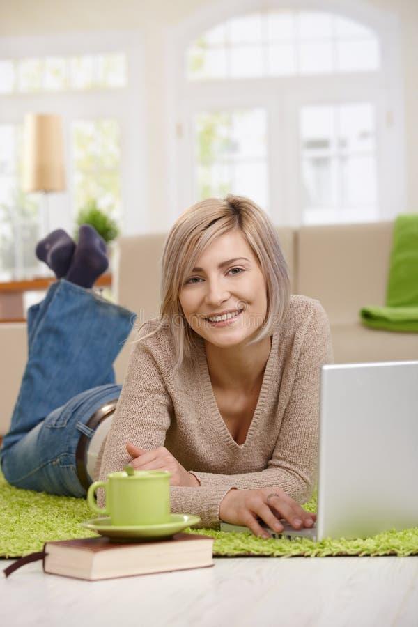 Mulher feliz que usa o portátil em casa foto de stock royalty free
