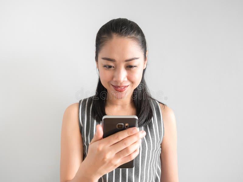 Mulher feliz que usa o smartphone foto de stock
