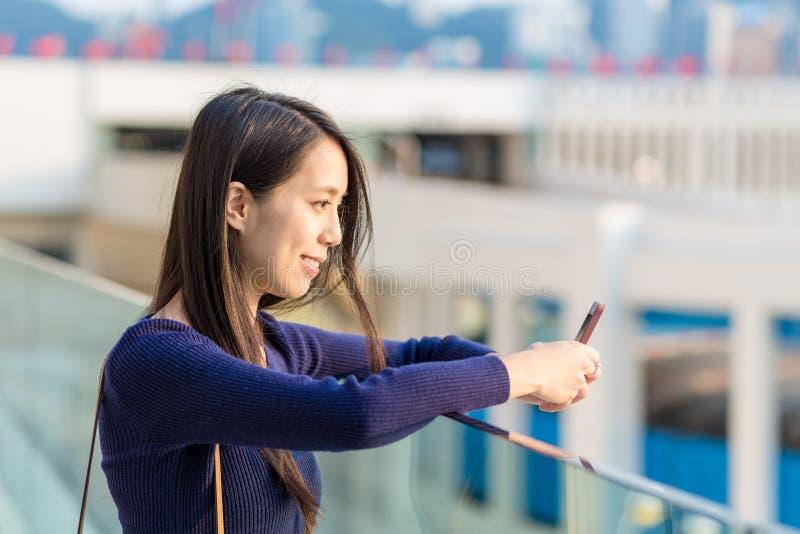 Mulher feliz que usa o telefone esperto na rua imagem de stock