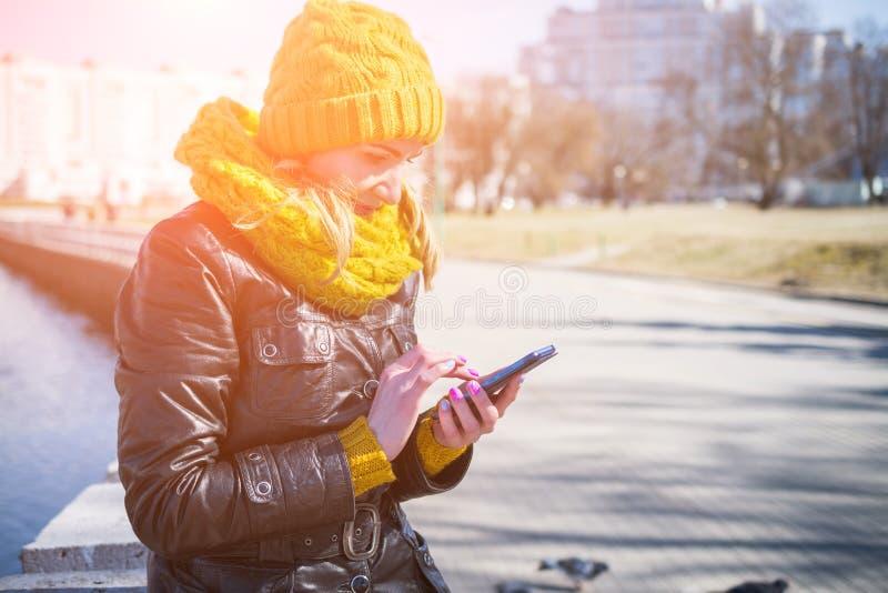 Mulher feliz que usa um telefone esperto na rua com um fundo unfocused fotos de stock royalty free