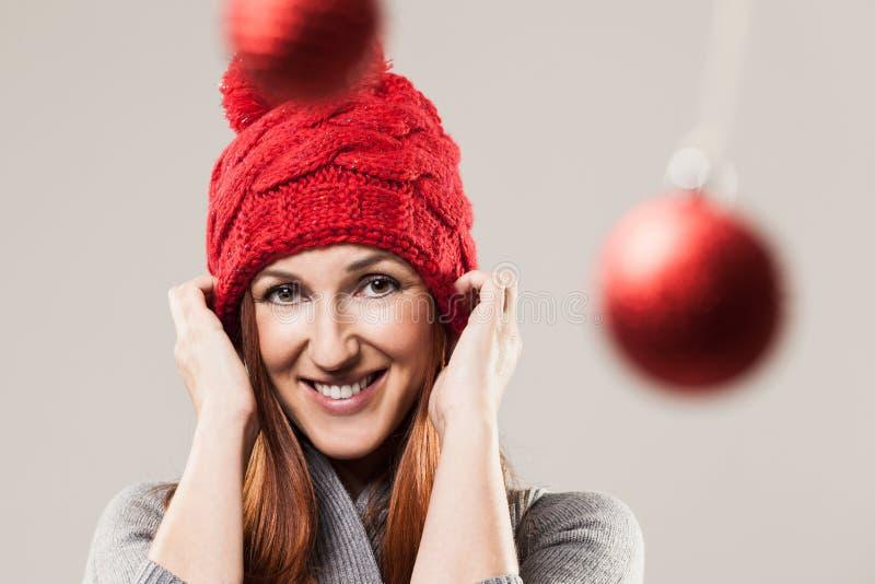 Mulher feliz que veste um tampão vermelho do beanie fotografia de stock