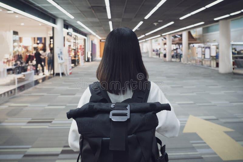 Mulher feliz que viaja e que anda no aeroporto Menina no chapéu com a trouxa que viaja no aeroporto imagens de stock