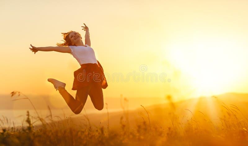 A mulher feliz salta, exulta, no por do sol na natureza imagens de stock royalty free