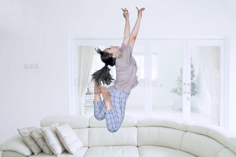 A mulher feliz salta na sala de visitas imagens de stock royalty free