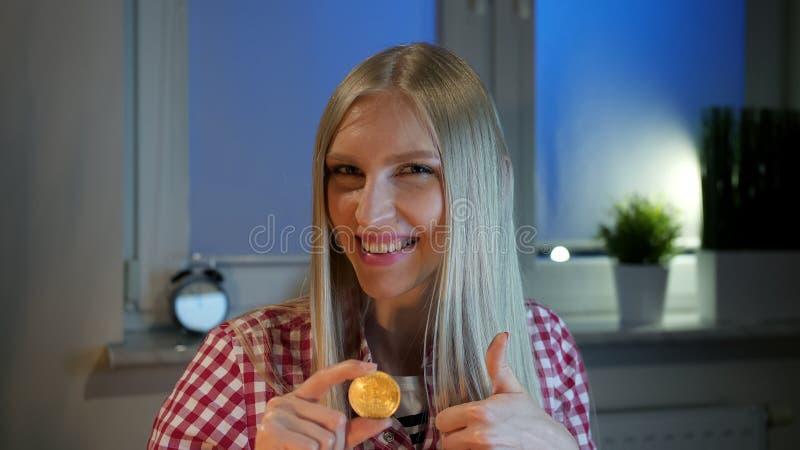 Mulher feliz segurando bitmoney mostrando polegares para cima Uma jovem loira animada, de roupas casuais, sentada à janela escura foto de stock