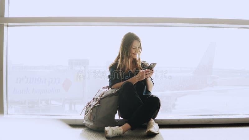 A mulher feliz senta-se com o smartphone pela janela do aeroporto Menina caucasiano com trouxa usando o mensageiro app no termina foto de stock royalty free