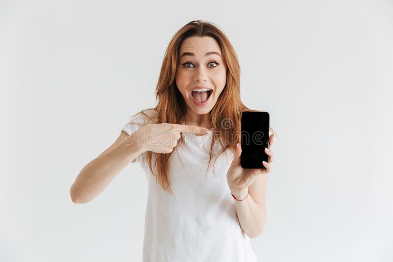 Mulher feliz surpreendida na roupa ocasional que mostra a tela vazia do smartphone imagem de stock royalty free