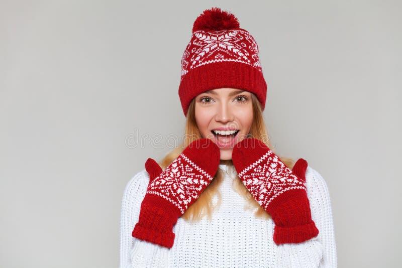 Mulher feliz surpreendida que olha lateralmente no excitamento Menina do Natal que veste o chapéu feito malha e os mitenes mornos imagem de stock