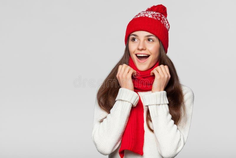 Mulher feliz surpreendida que olha lateralmente no excitamento Vestir da menina do Natal fez malha o chapéu morno e o lenço, isol foto de stock