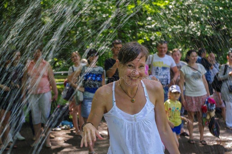 A mulher feliz tem o divertimento que joga na fonte de água do parque no dia de verão quente fotografia de stock royalty free