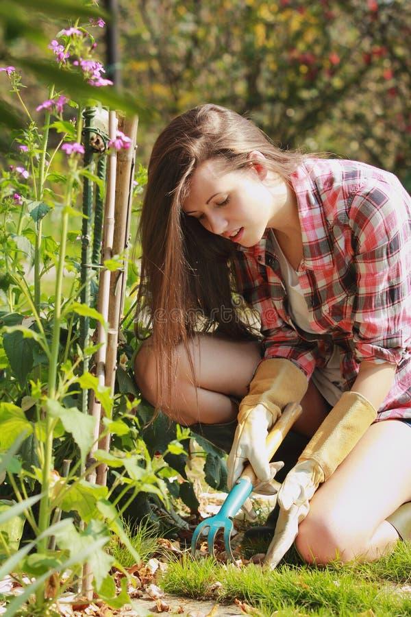 A mulher feliz trabalha em seu jardim fotos de stock