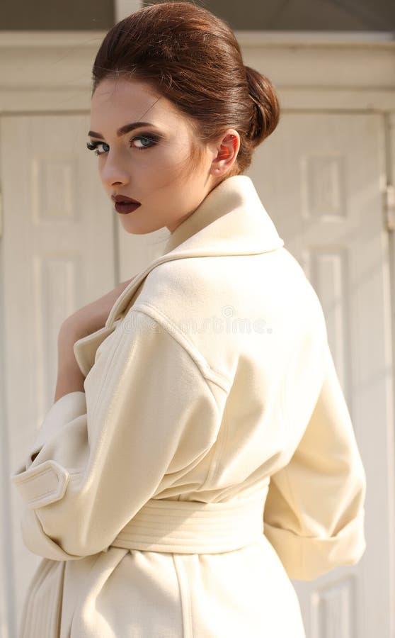 A mulher feminino bonita com cabelo escuro em lãs luxuosos reveste foto de stock royalty free
