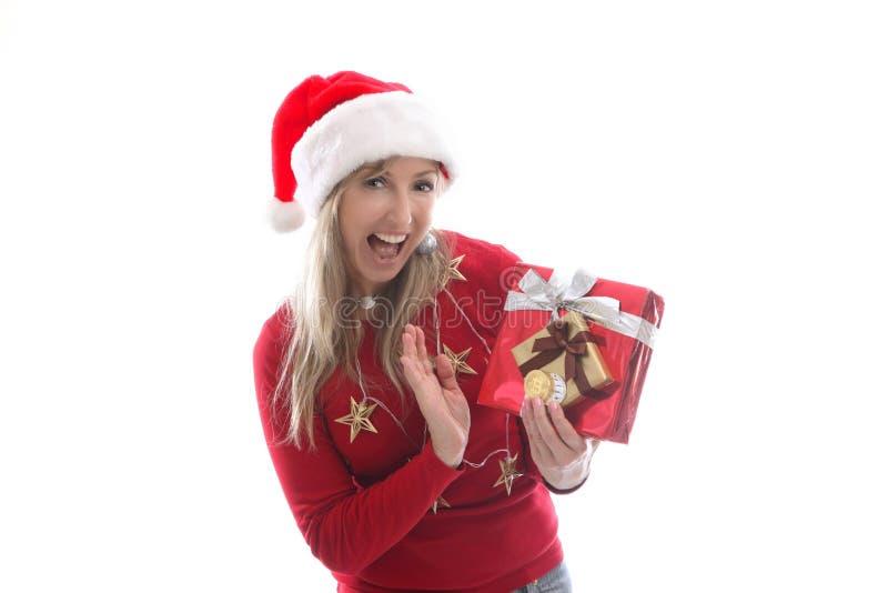 Mulher festiva no Natal está guardando moedas criptos da moeda e um presente fotos de stock