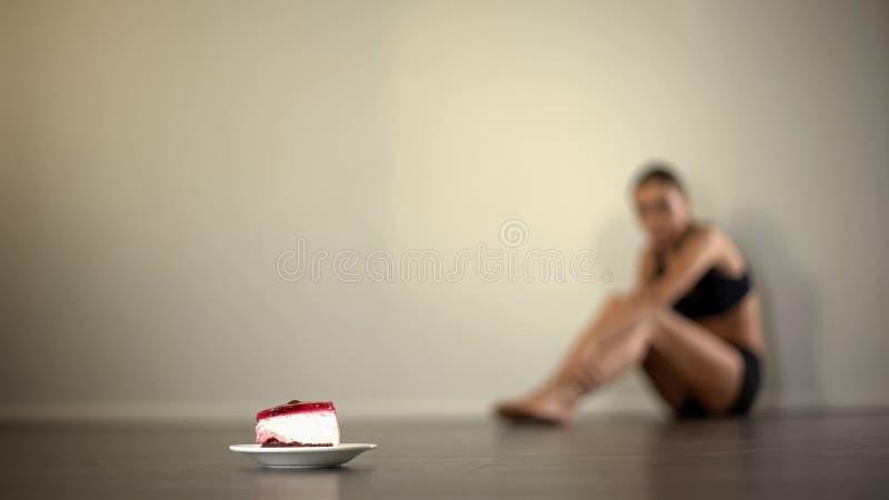 Mulher fina que olha a parte saboroso do bolo, sonhando para comer doces, dieta insalubre imagens de stock royalty free