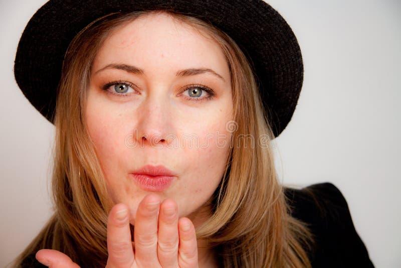 A mulher flertando nova está desgastando um chapéu foto de stock royalty free