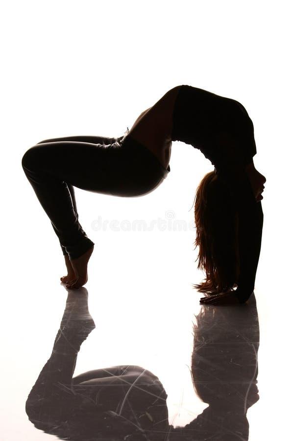 Mulher flexível que estica a silhueta imagem de stock royalty free