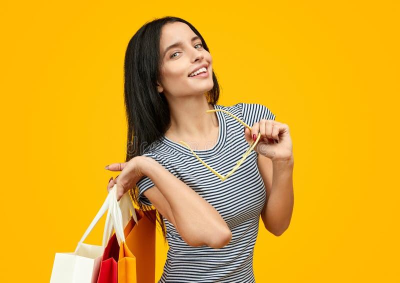 Mulher Flirty com os sacos de papel que olham a câmera fotos de stock