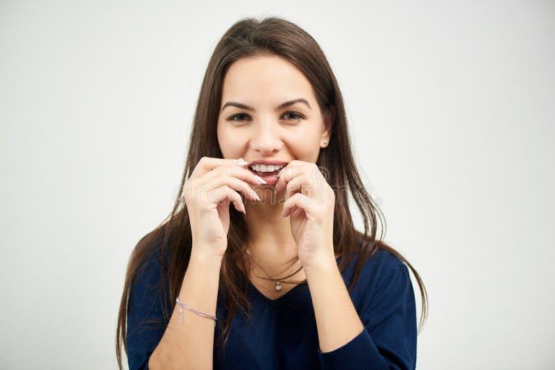 A mulher flosses seus dentes com fio dental no fundo branco fotos de stock royalty free