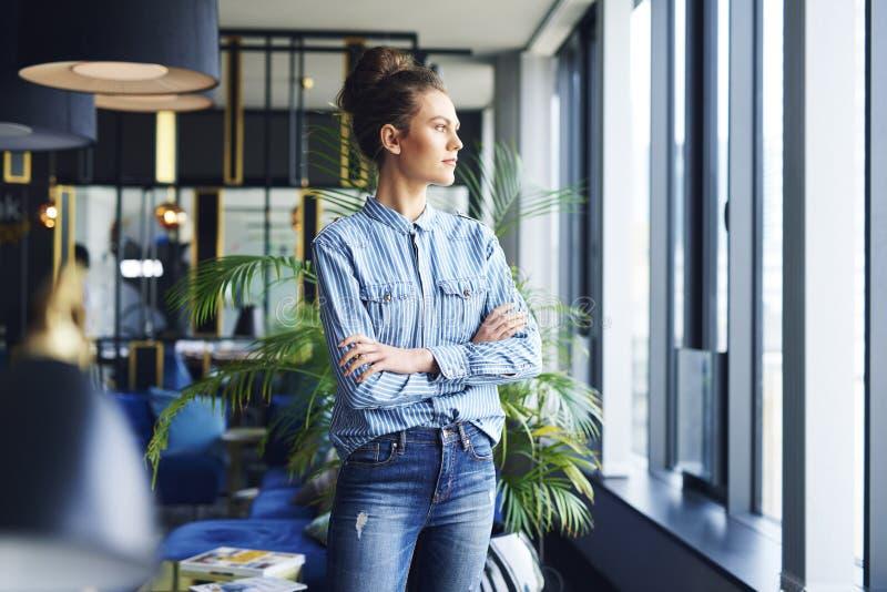 Mulher focalizada que olha através da janela no escritório imagens de stock royalty free