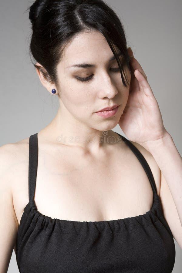 Mulher forçada com uma dor de cabeça fotografia de stock