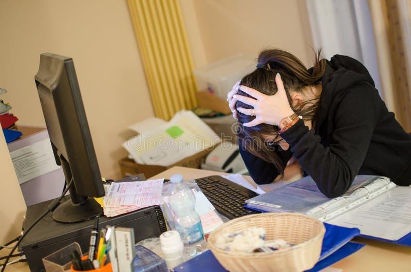 Mulher forçada no trabalho com o computador na frente dela imagens de stock royalty free