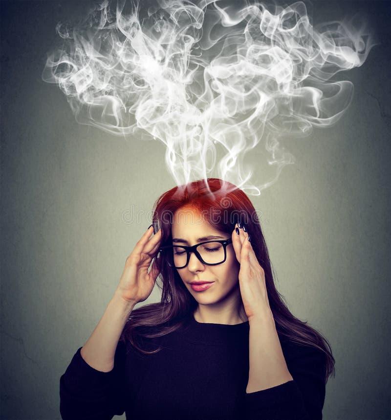 Mulher forçada que pensa o vapor demasiado duro que sai acima da cabeça fotografia de stock royalty free
