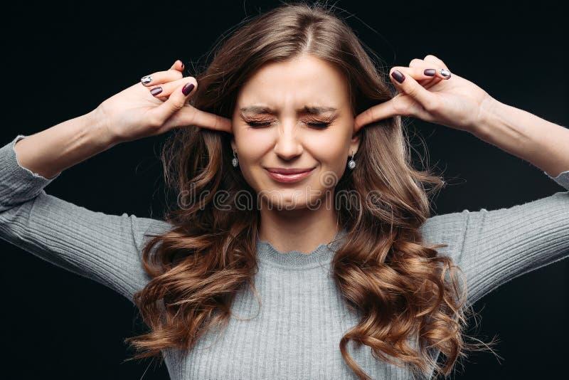 Mulher forçada que sente as emoções negativas isoladas no fundo cinzento foto de stock royalty free