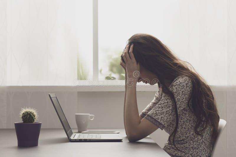 Mulher forçada Tired que senta-se na mesa e na conexão fotografia de stock royalty free