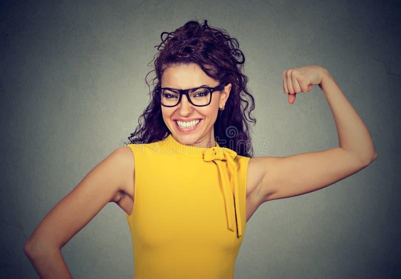 Mulher forte bem sucedida feliz que dobra seu bíceps foto de stock