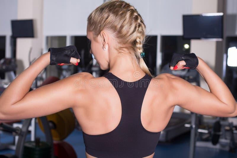 A mulher forte com corpo bonito mostra-lhe os músculos imagem de stock royalty free