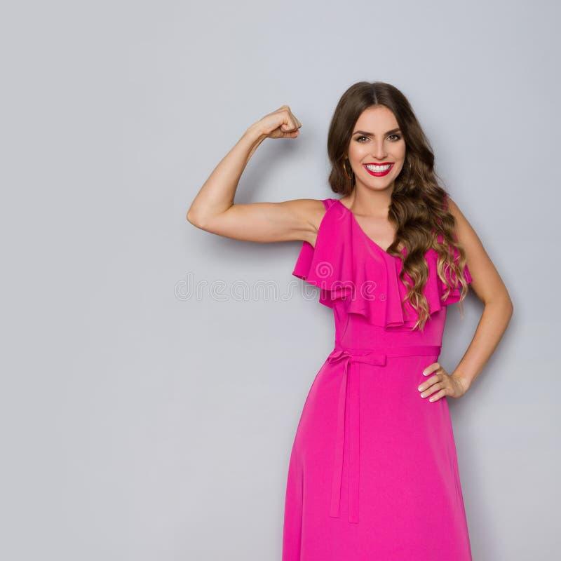 A mulher forte no vestido cor-de-rosa elegante está dobrando os músculos e o sorriso foto de stock royalty free