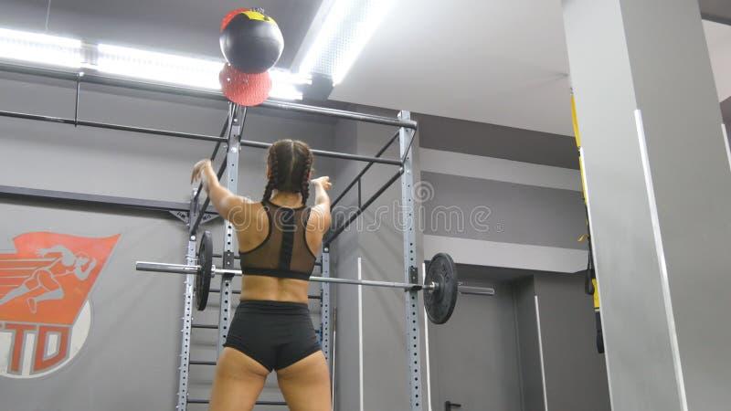 Mulher forte nova com o corpo perfeito da aptidão no sportswear que exercita com a bola de medicina no gym Menina que faz o cross imagem de stock