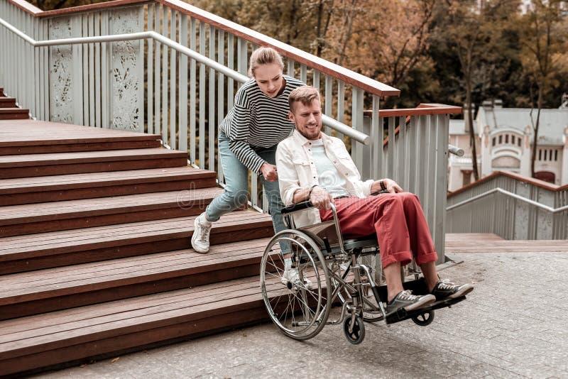 Mulher forte que ajuda o homem inválido e que leva sua cadeira de rodas imagem de stock
