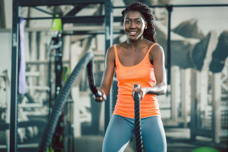A mulher forte que exercita com batalha ropes durante o treinamento funcional imagem de stock royalty free