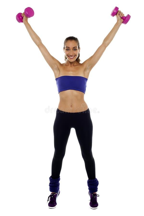 Mulher forte que levanta os dumbbells altamente no ar fotografia de stock