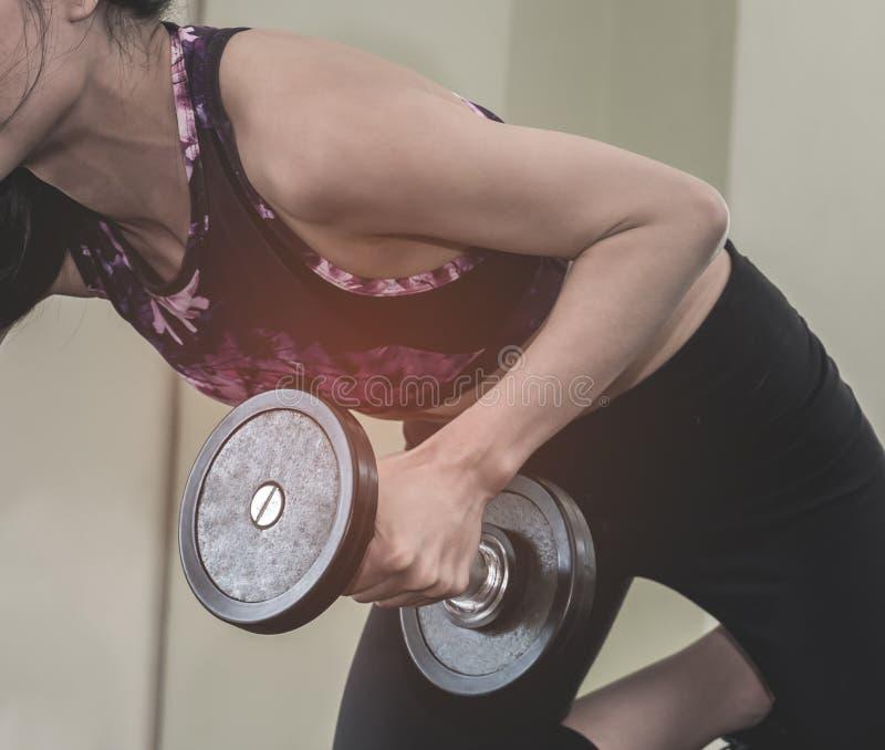 Mulher forte que levanta um peso do peso com seu braço esquerdo foto de stock