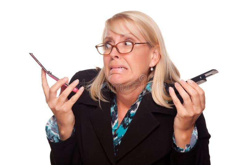 Mulher frustrante com os dois telefones de pilha foto de stock