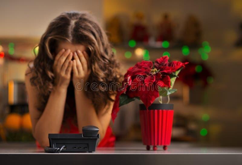 Mulher frustrante que espera um telefonema na cozinha do Natal fotografia de stock royalty free