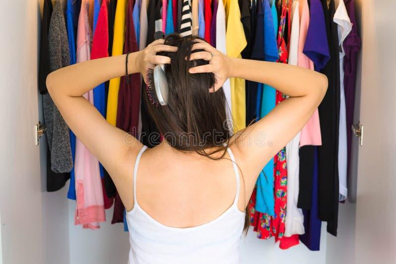 Mulher frustrante que está na frente de seu armário, tentando encontrar algo vestir foto de stock royalty free
