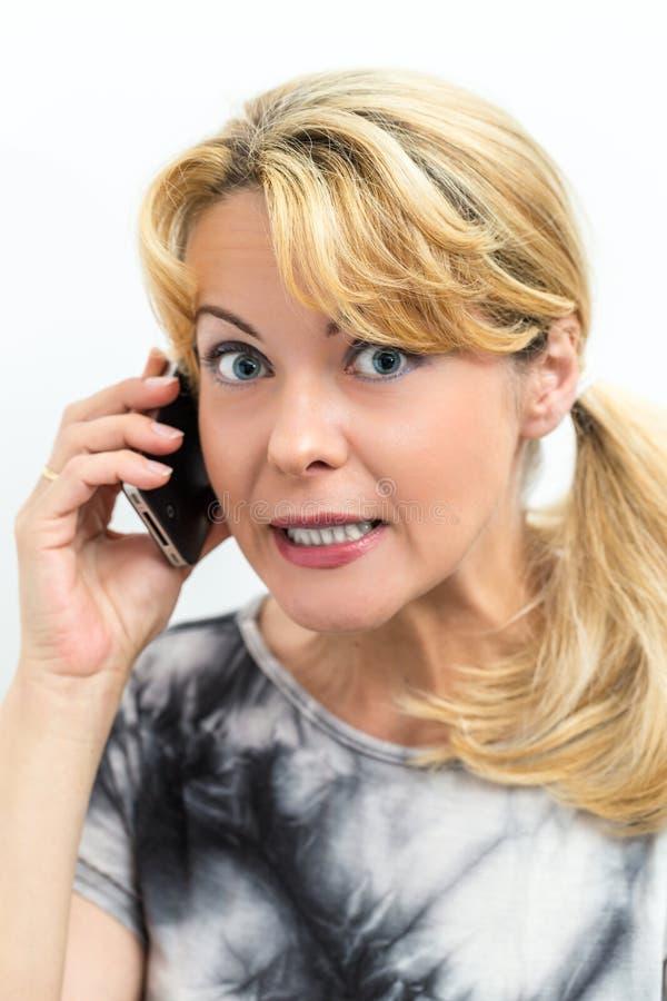 Mulher frustrante que fala em seu telefone celular fotografia de stock