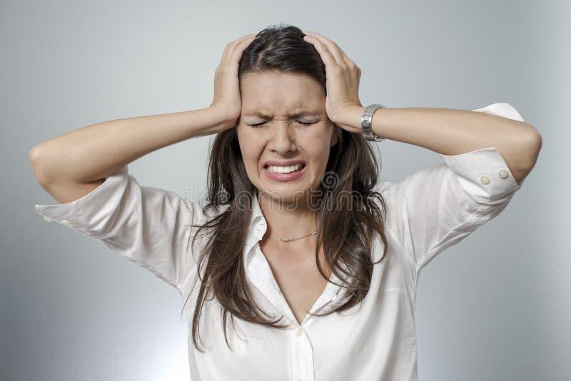 Mulher frustrante que toma sua cabeça entre suas mãos foto de stock royalty free
