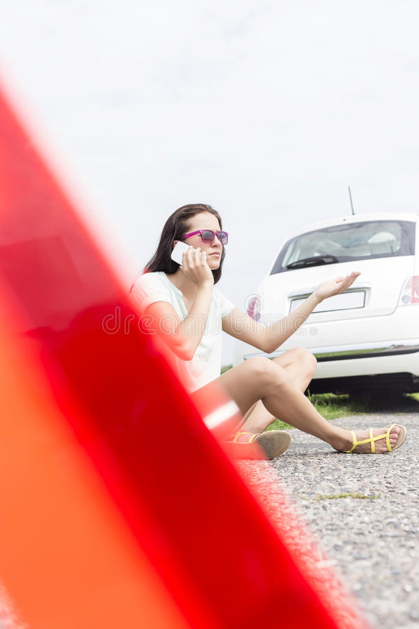 Mulher frustrante que usa o telefone celular ao sentar-se pelo carro dividido imagem de stock royalty free