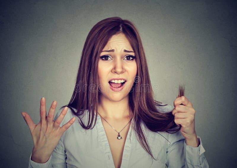 A mulher frustrante surpreendeu-a é extremidades rachadas do cabelo perdedor imagens de stock