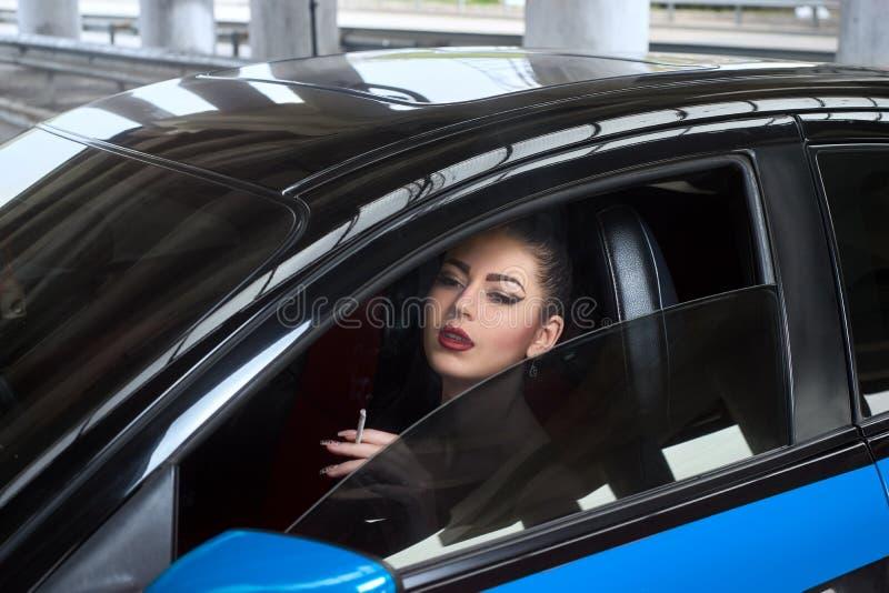 A mulher fuma no carro fotos de stock