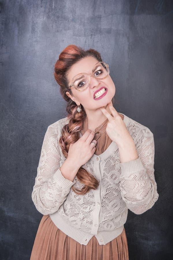 A mulher furada engraçada que guarda dois dedos aproxima a garganta no quadro foto de stock royalty free
