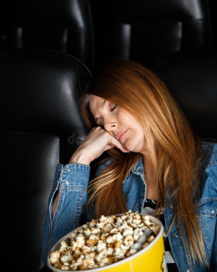 Mulher furada que dorme no teatro do cinema imagem de stock