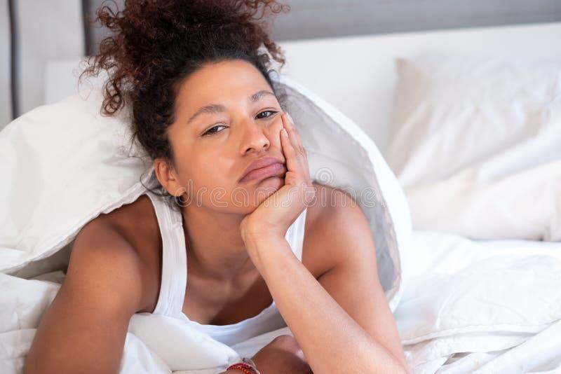 Mulher furada que senta-se na cama na manhã imagem de stock royalty free
