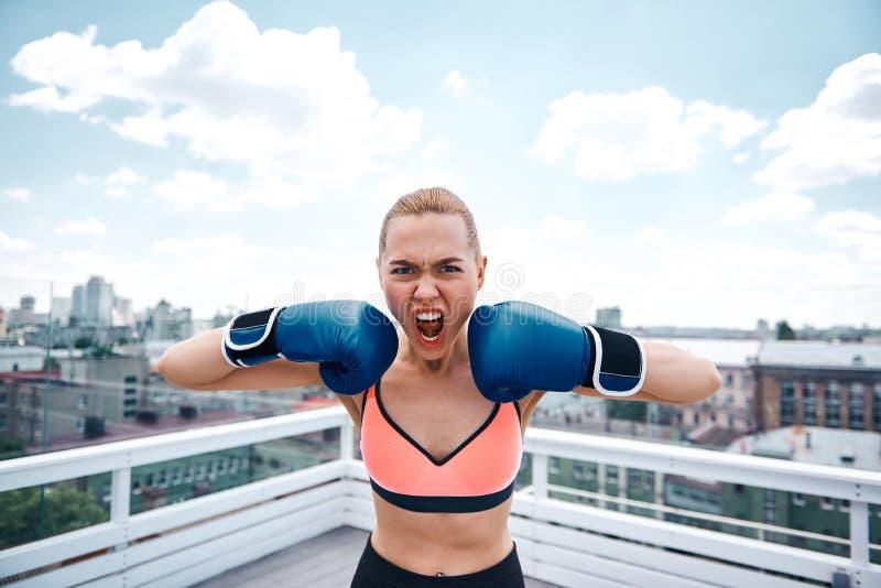 A mulher furioso é gritaria ao encaixotar no telhado urbano fotografia de stock royalty free