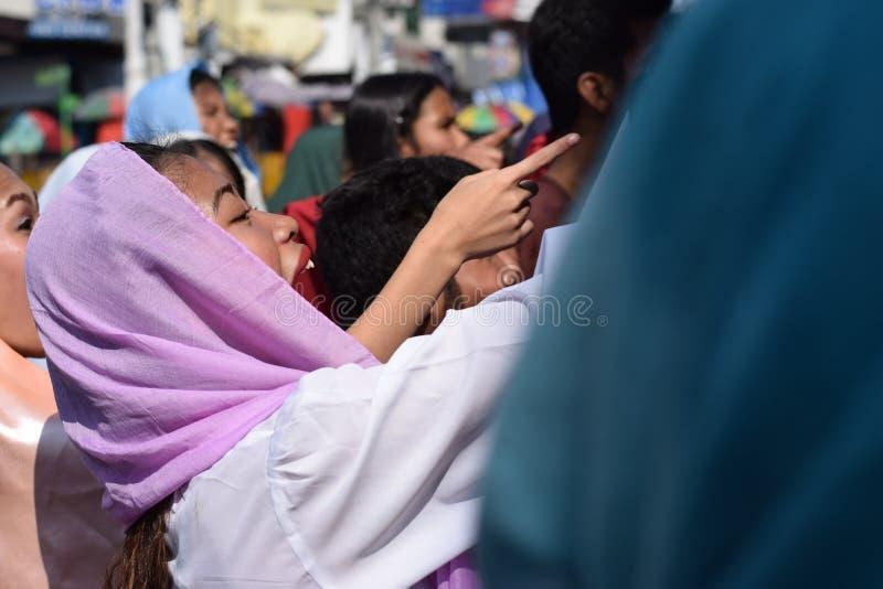 A mulher furioso que persegue Jesus Christ que cheering, debochante entre a multidão, drama da rua, a comunidade comemora o Sexta fotografia de stock