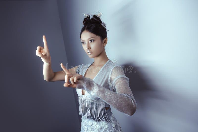 Mulher futurista asiática bonita nova que pressiona um botão imaginário, espaço vazio para botões foto de stock royalty free